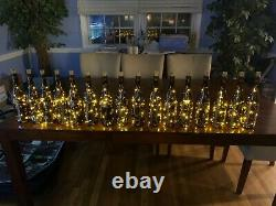 Wine bottle centerpieces with table numbers and string lights